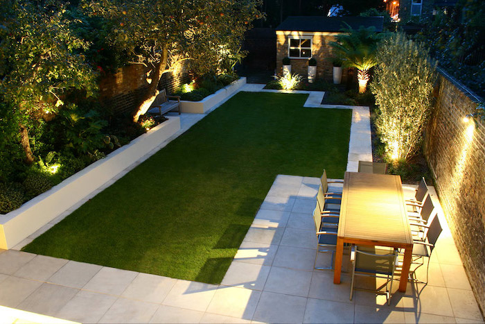 lots of lights, patch of grass, garden furniture, on a tiled floor, small backyard designs, planted trees and bushes