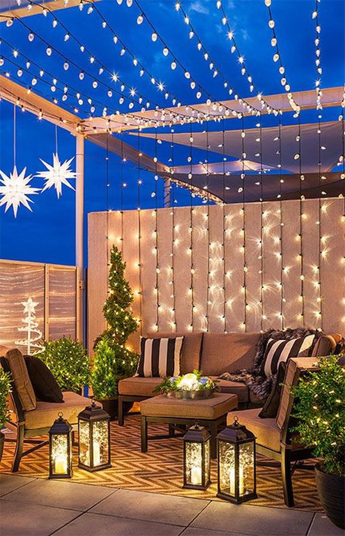 many strings of lights, over garden furniture, with throw pillows, small space gardening, potted plants