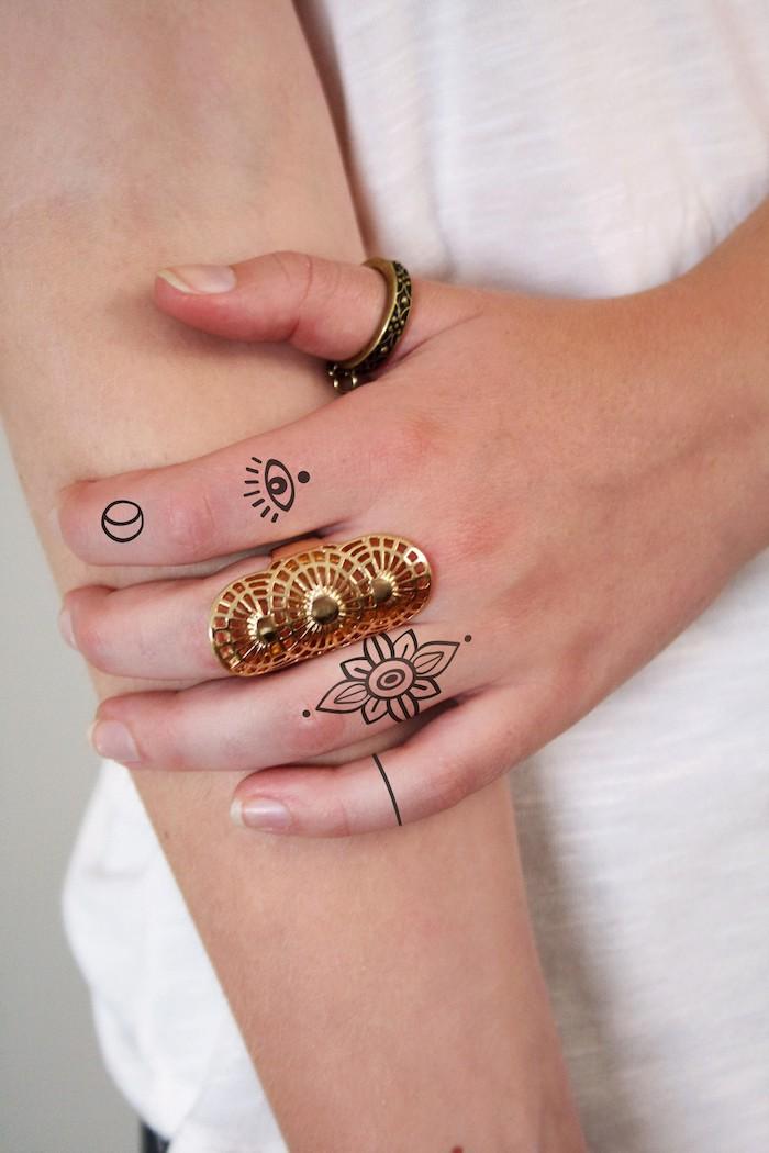 large golden ring. flower eye and moon finger tattoos, heart tattoo on finger, white shirt
