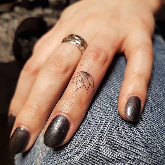 lotus flower, ring finger tattoo, heart tattoo on finger, grey nail polish, hand resting on jeans