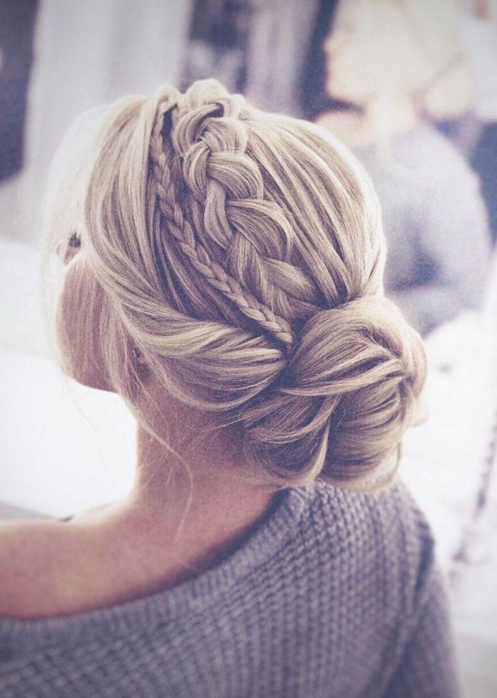blonde hair in a low bun, small and big braid, grey sweater, wedding hairdos, blurred background