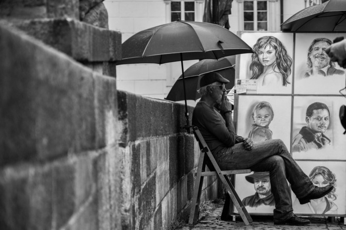 man sitting on a chair, smoking a cigarette, surrounded by drawings of celebrities, girl drawing