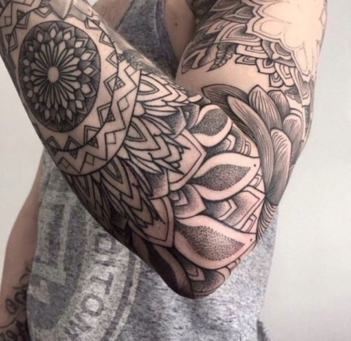 large black and white, arm sleeve tattoo, man wearing a grey top, cool small tattoos, white background