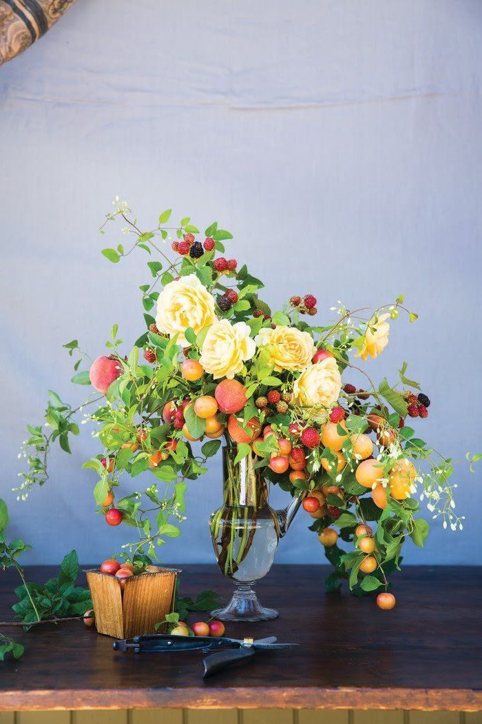 tall vintage vase, filled with flowers and fruits, in different colours, flower arrangements