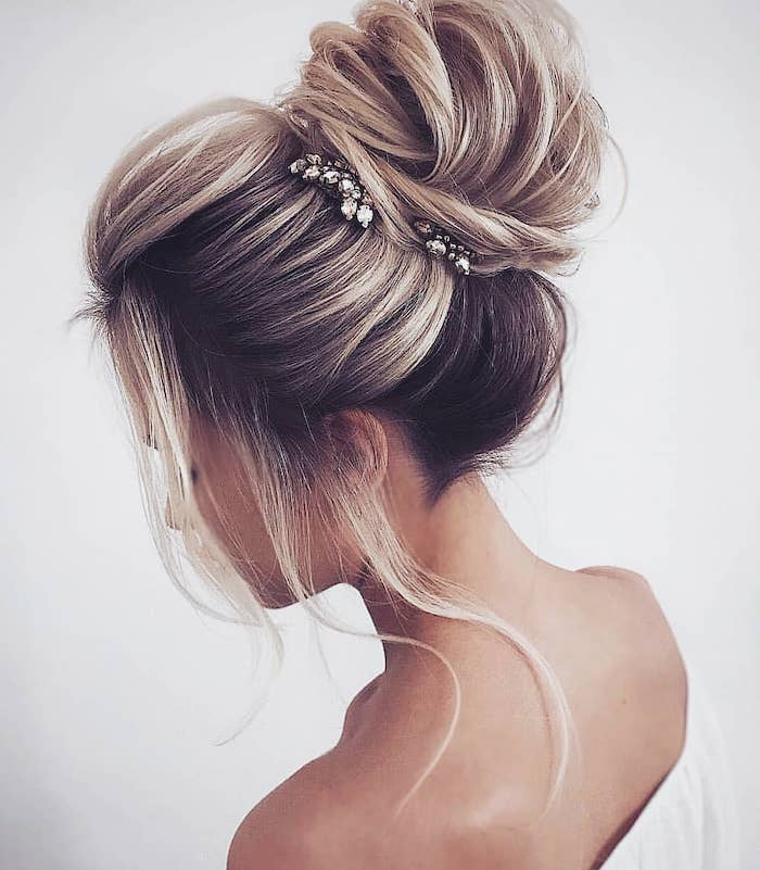 white top, wedding hairstyle, messy bun, small hair accessories, loose strands of hair