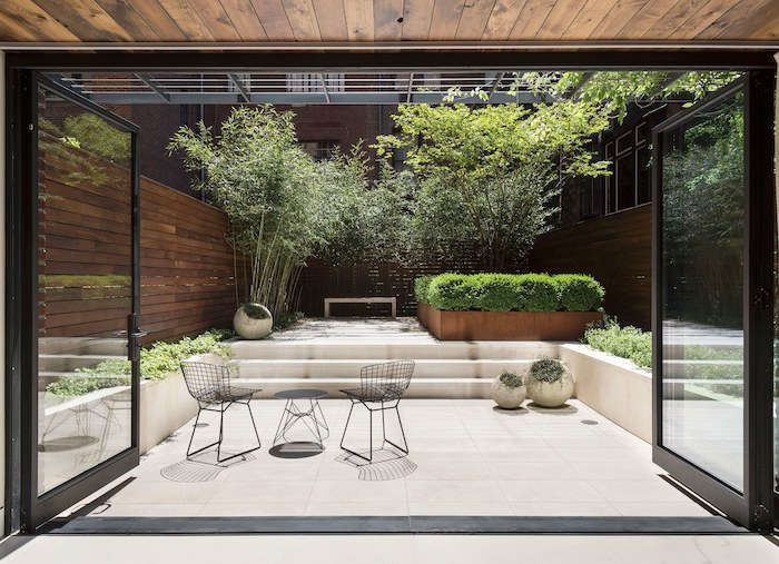 metal black garden furniture, small garden ideas, large windows, planted trees and bushes, cement tiles