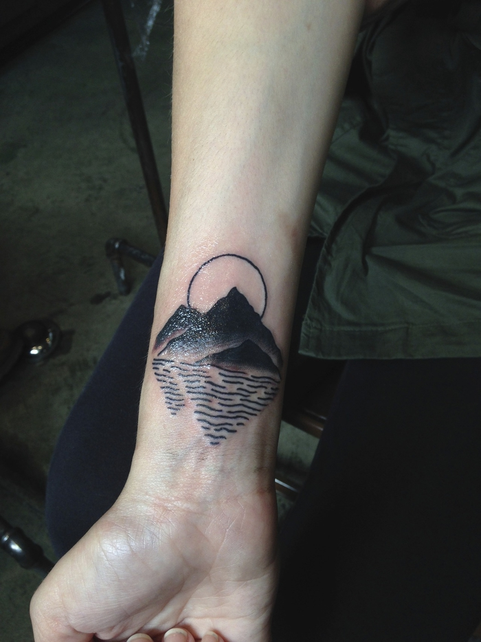 mountain landscape with river, geometric flower tattoo, tattoo on the wrist of a girl