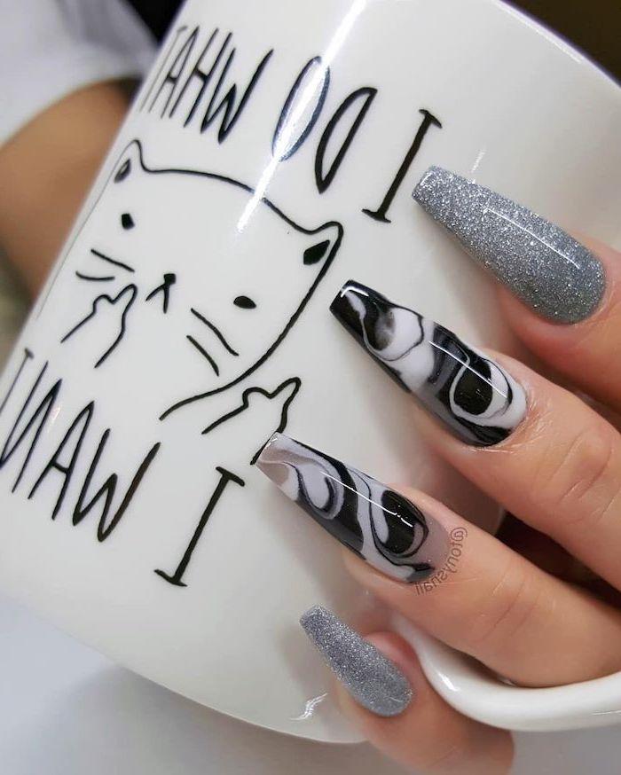 hand holding a mug, cute coffin nails, marble like nails, silver glitter nail polish, long coffin nails