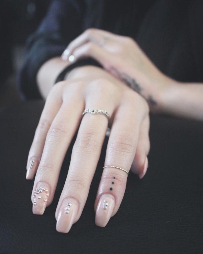 small dots, tattoo on the finger, cute finger tattoos, nude nail polish with rhinestones, black shirt