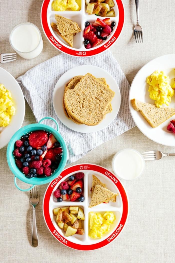 scrambled eggs, bread slices, nutrition plan, blue bowl, full of blackberries and strawberries, glasses of milk