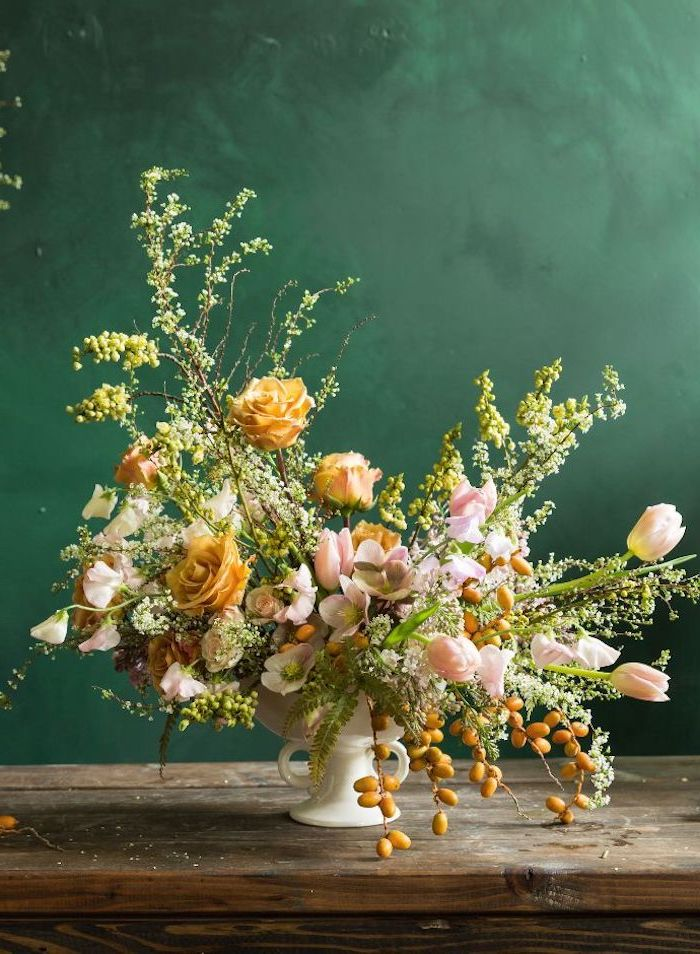 large orange and pink flower bouquet, in a small white vase, on a wooden table, flower arrangement ideas