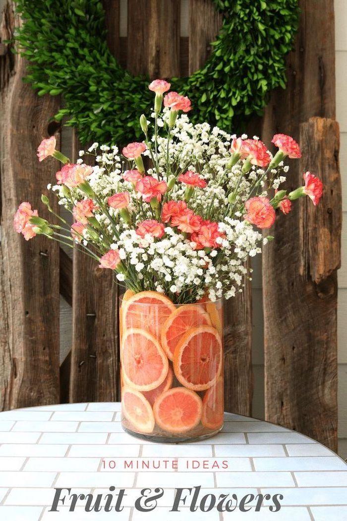 large round vase, filled with orange slices, flower arrangement ideas, orange carnation flowers and baby's breath