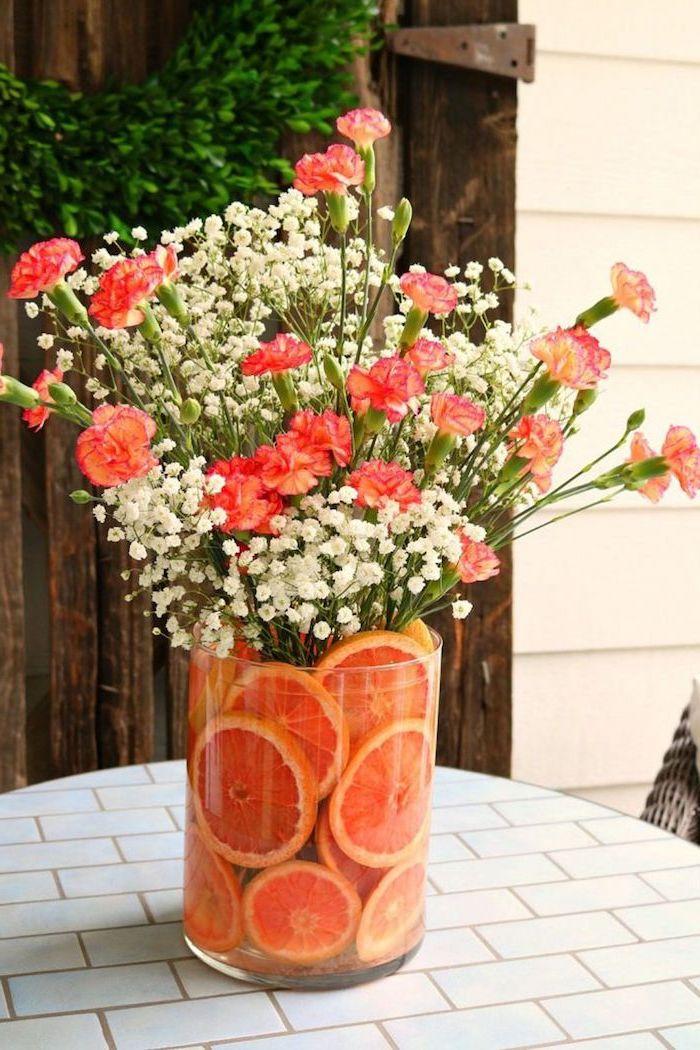 large round glass vase, filled with orange slices, orange carnation flowers, and baby's breath, floral arrangements