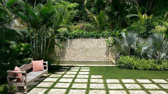 cement tiles, over a patch of grass, small wooden bench with pink throw pillows, small backyard designs, planted palm trees