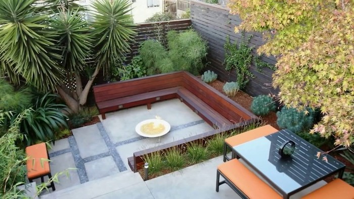large wooden bench, fire pit in the middle, small backyard designs, planted palm trees and bushes