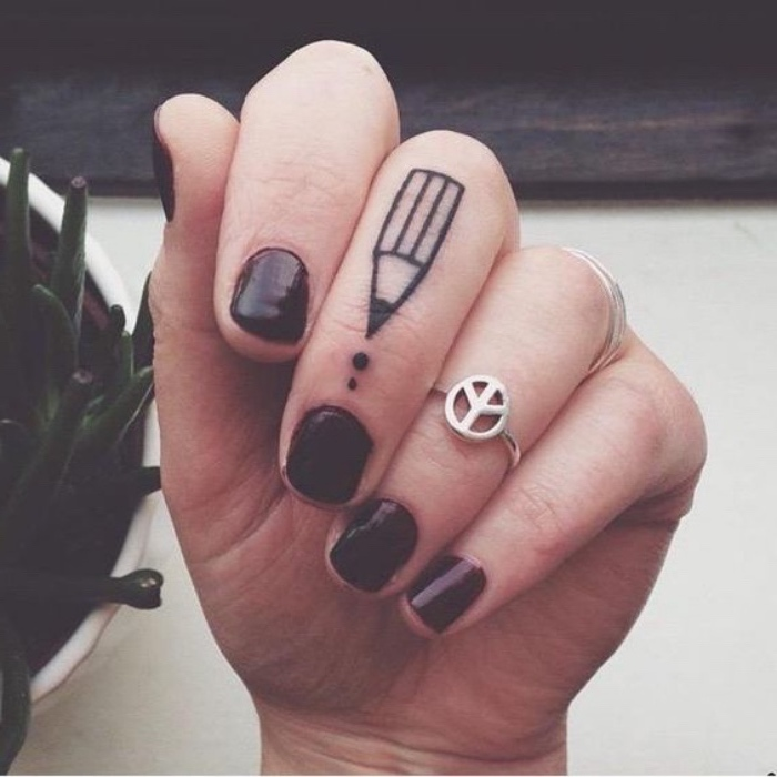 pencil finger tattoo, woman wearing burgundy nail polish, small butterfly tattoos, silver rings