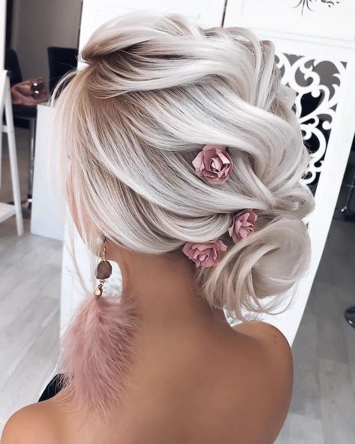 platinum blonde hair, pink feather earrings, wedding hairstyles, hair in a low updo, pink flowers in hair