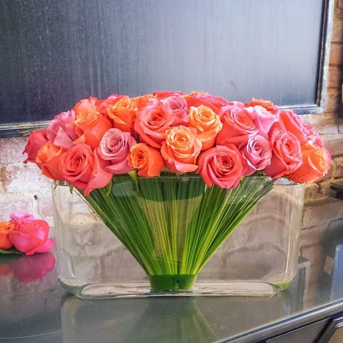 pink and orange roses, in a large glass vase, how to arrange flowers, on a grey countertop