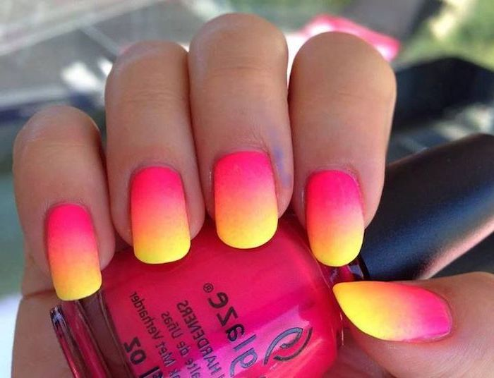 pink orange and yellow ombre, neon nail polish, long squoval nails, pink and gold nails, hand holding a pink nail polish bottle