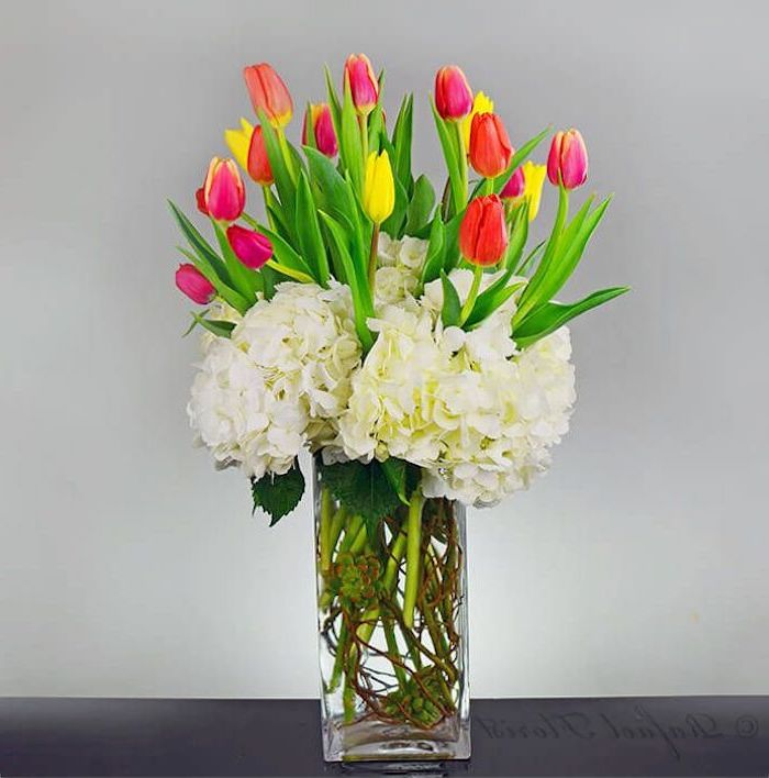 pink and yellow tulips, flower bouquet, in a square glass vase, in front of a white background, how to arrange flowers