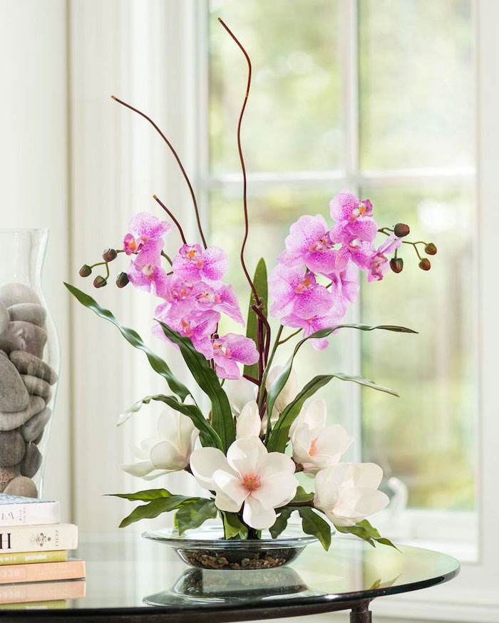 purple orchids and white magnolias, in a small glass plate, floral arrangements, on a glass coffee table