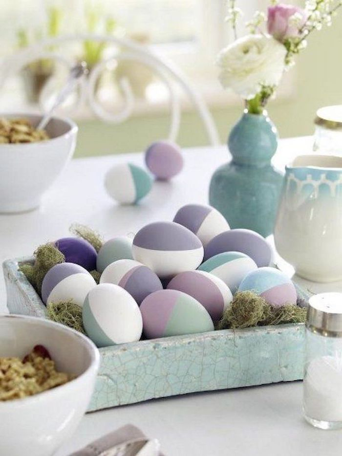 natural easter egg dye, purple and blue, pink and green, geometrical design eggs, in a ceramic bowl, full of moss