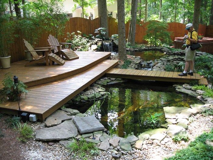 small ponds, wooden bridge over them, wooden lounge chairs, backyard ideas for small backyards