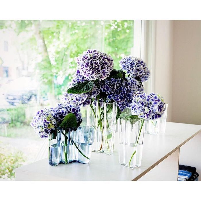 purple flowers, in three separate glass vases, how to make flower arrangements, on a white wooden table