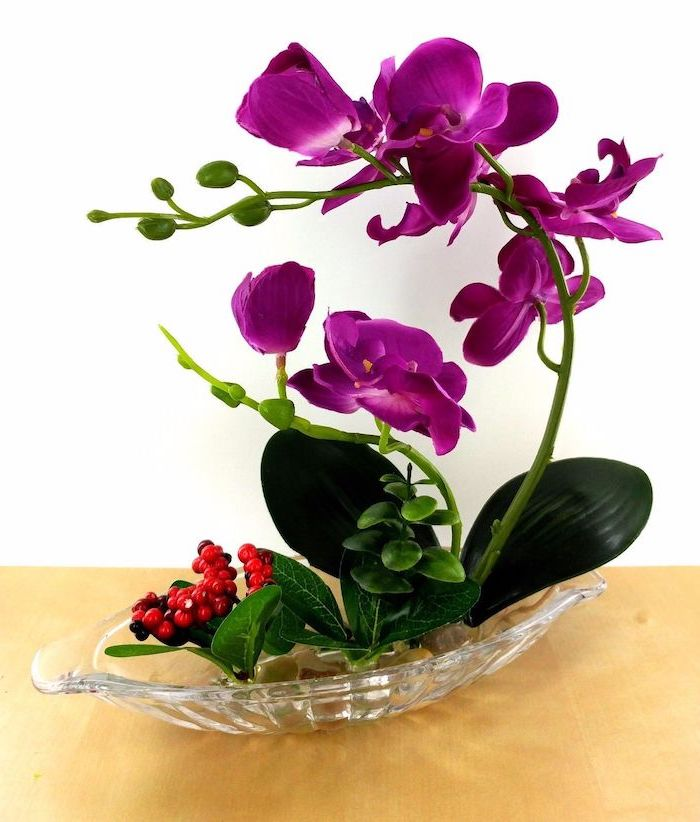 purple orchid, in a very small glass plate, with river stones, beautiful flower arrangements, on a wooden table