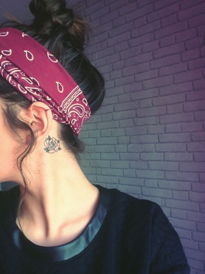 rose behind the ear tattoo, red bandana on the brown hair, in a messy bun, small sunflower tattoo