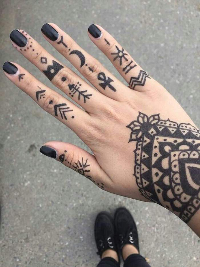 lots of tattoos, on each finger, black nail polish, black sneakers, lion finger tattoo