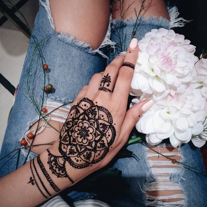 large henna tattoo, pink nail polish, lion finger tattoo, hand holding a flower bouquet