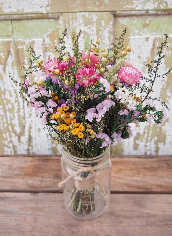 small colourful flower bouquet, in a mason jar, beautiful flower arrangements, on a wooden table, in a rustic style