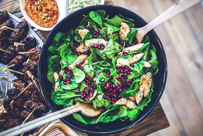 pomegranate seeds, basil salad, with meat, in a large black bowl, healthy eating meal plan