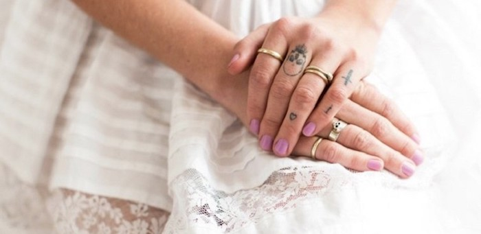 hands resting on a white dress, cross heart and skull, finger tattoos, rose finger tattoo, pink nail polish