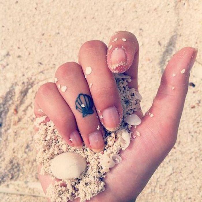 small seashell, ring finger tattoo, rose finger tattoo, hand holding beach sand, small seashells