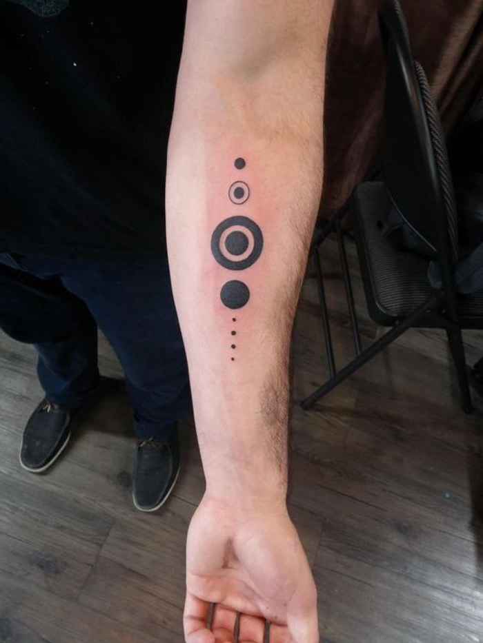 circles and dots tattoo, on the forearm, geometric owl tattoo, wooden floor, man standing