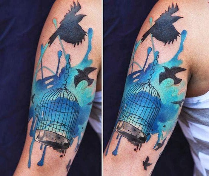 bird cage, birds flying away, watercolour shoulder tattoo, inner arm tattoos, blue background