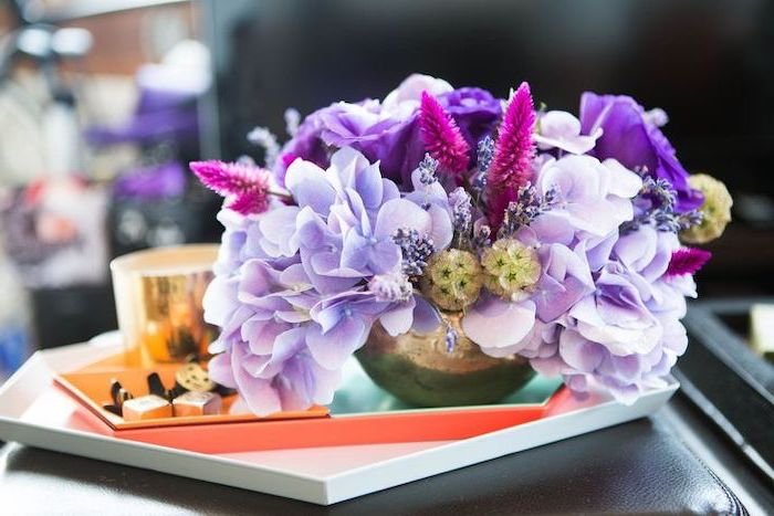 small purple flower bouquet, in a small brass vase, diy flower arrangements, on a small leather stool