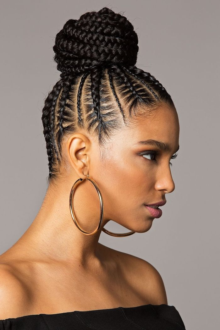 braided black hair, in a bun, large hoops earrings, easy to do hairstyles, grey background