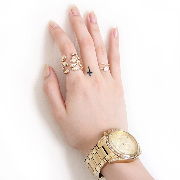 large golden watch, small cross, middle finger tattoo, couple finger tattoos, golden rings