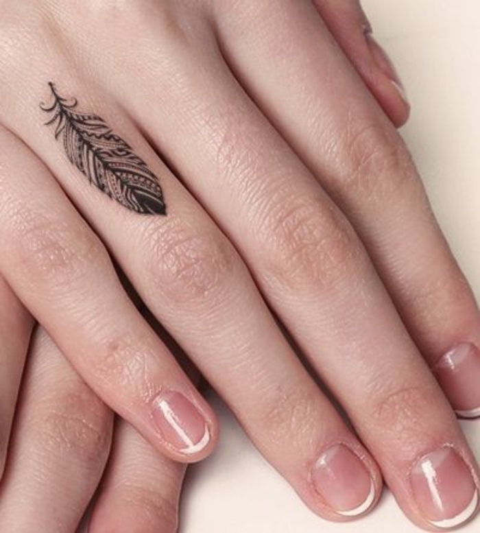 small feather, ring finger tattoo, couple finger tattoos, hands on top of one another, in front of a white background