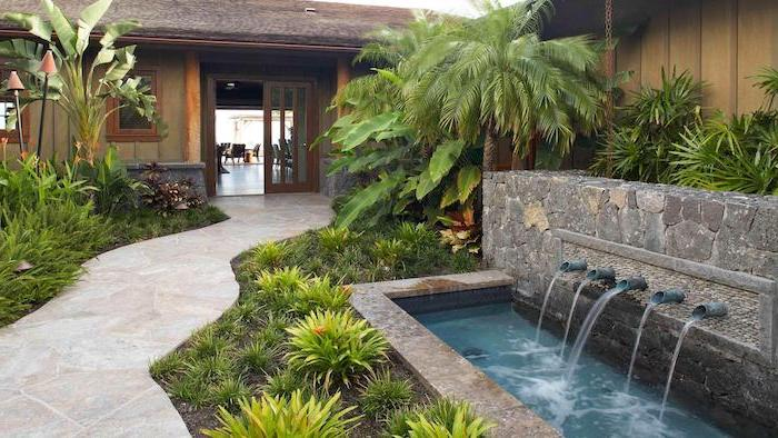 small fountains, cement tiled pathway, planted bushes and palm trees alongside it, backyard ideas for small backyards