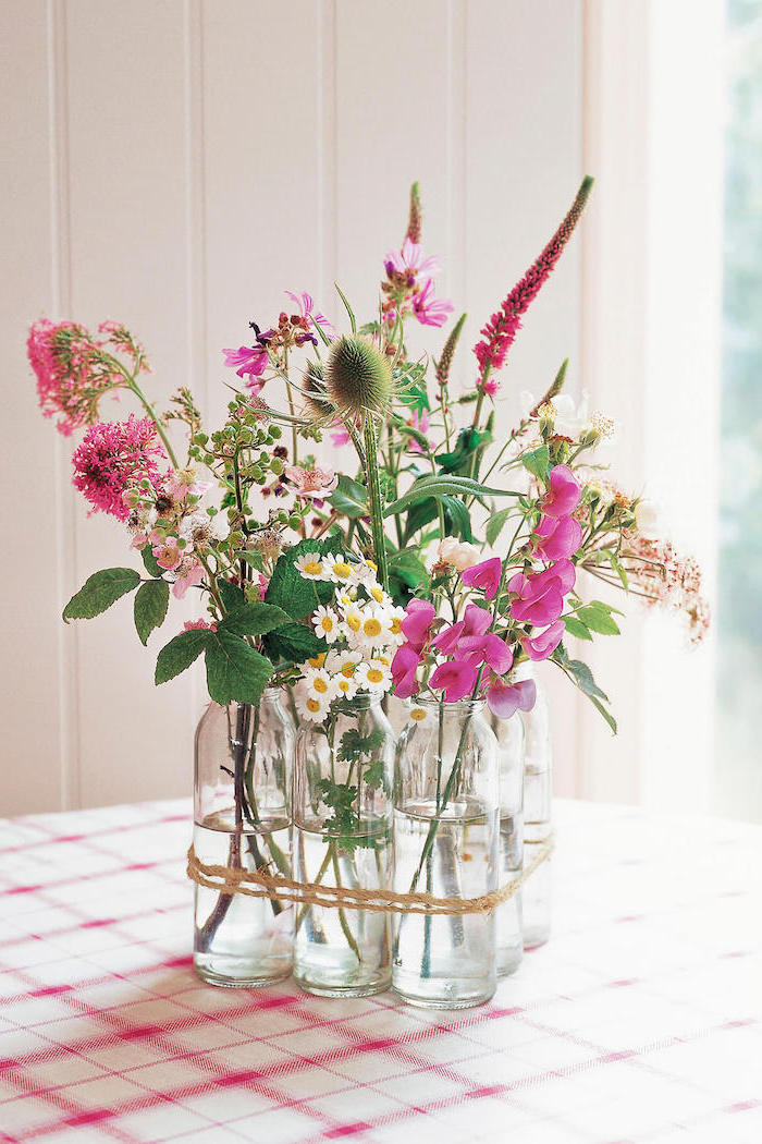 glass bottles arranged in a one centerpiece, different colourful flowers, diy flower arrangements