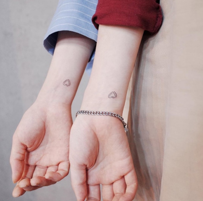hearts matching wrist tattoos, hands in front of a grey background, cool small tattoos for guys