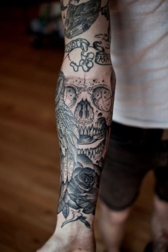 arm sleeve tattoo, with skull owl and roses, upper arm tattoos, man wearing a white shirt and jeans