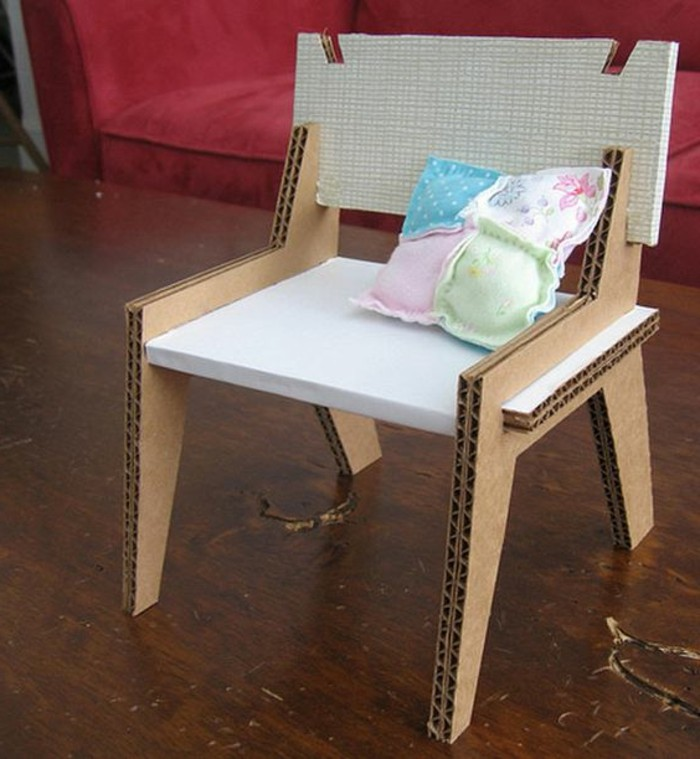 dark wooden floor, diy cardboard shelves, cardboard chair, small colourful throw pillow