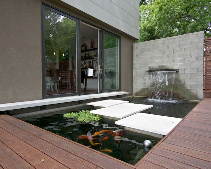 small pond, with a water fountain, cement tiles over the pond, small backyard landscaping, tall windows