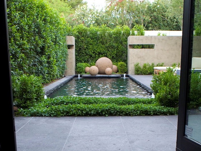 small pool, with small fountains, large round rocks, small backyard landscaping, surrounded by tall hedges