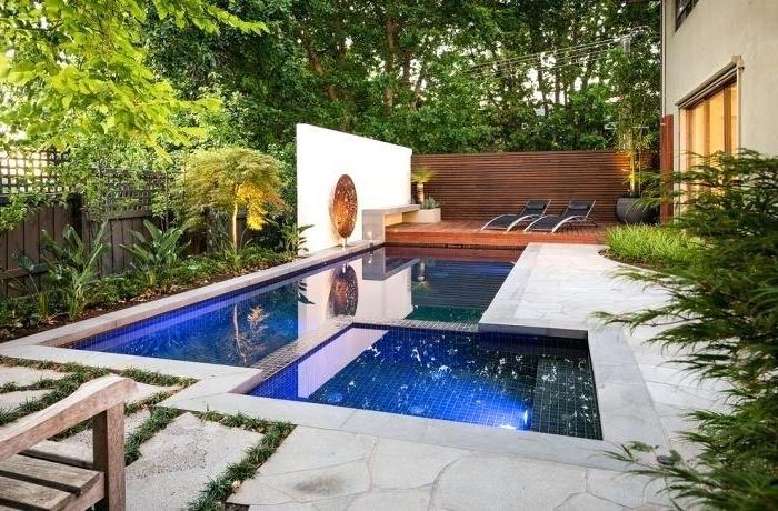 small swimming pool, with a small hot tub, small yard landscaping, two black lounge chairs